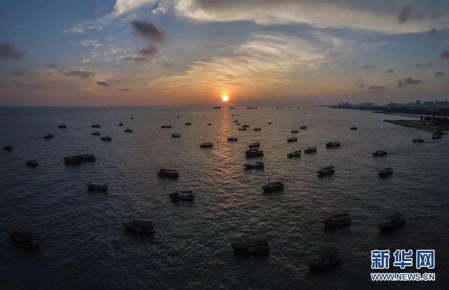 夕阳西下时,渔船从北海市银滩风景区出海作业.