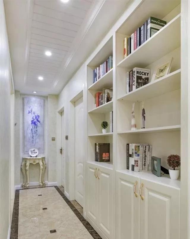 走廊设计了一组嵌入式书柜,还可以放些小饰品装饰,走廊尽头的端景桌图片