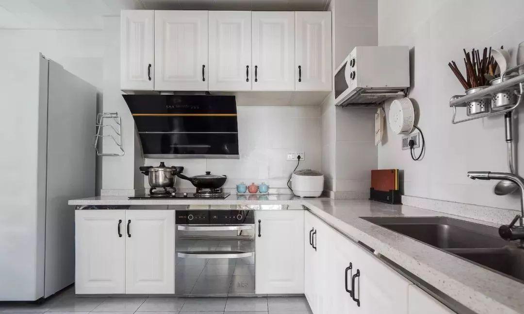 厨房地面通铺灰色瓷砖,立面浅色瓷砖搭配白色橱柜,灰色麻点台面耐
