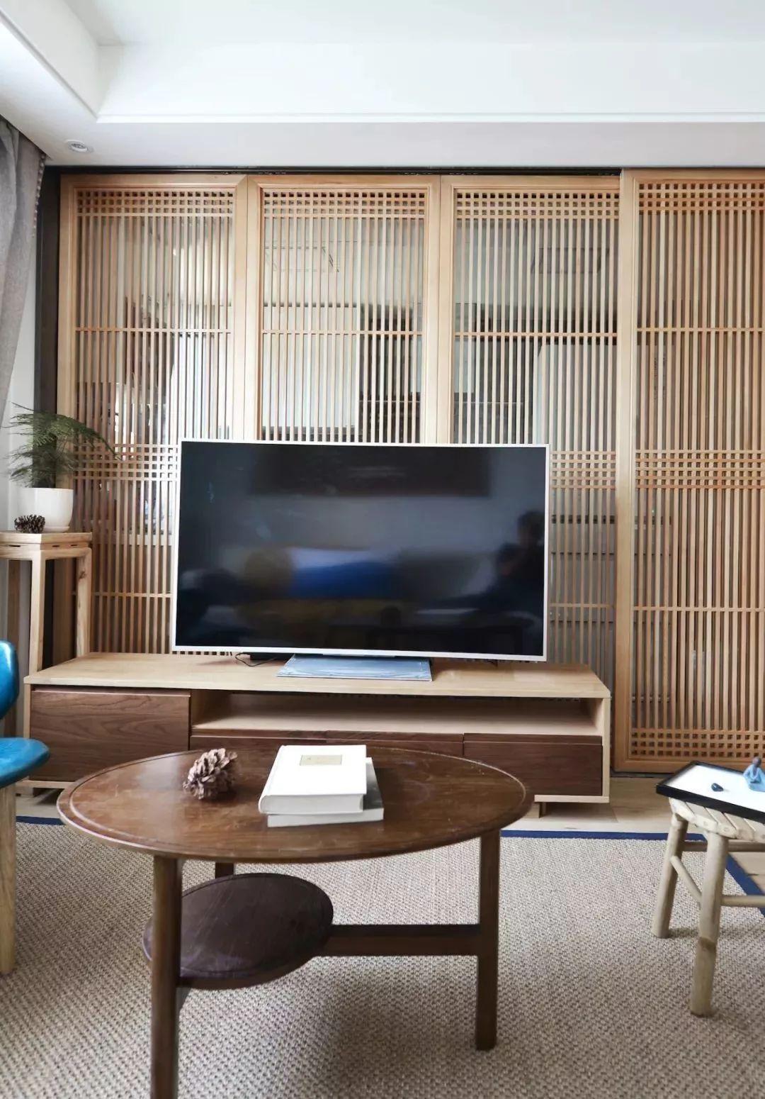 采用木质栏栅结合玻璃的移门作电视背景墙,充满韵味