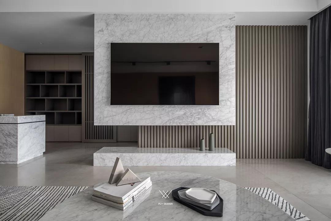 灰色的大理石电视墙和电视柜,不对称地做了木质屏风造型,带来别有