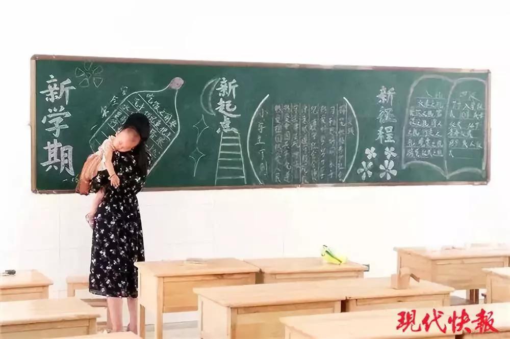 女老师抱娃出黑板报   她说:其实微不足道   黑板报前,   一位女老师