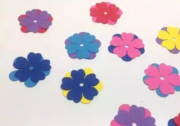 制作步骤:用不同颜色卡纸剪一些五瓣花叠在一起