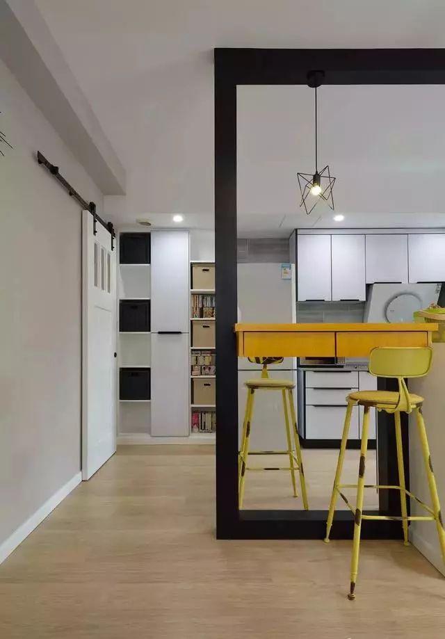 木作黑色隔断框架,分隔客厅与开放式厨房场域,并创造一种框景效果.
